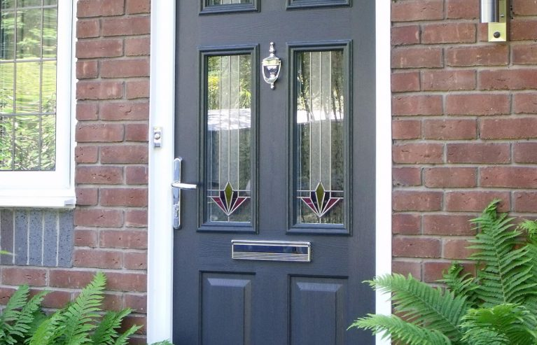 A dark grey front door with decorative glazed panels and chrome handle