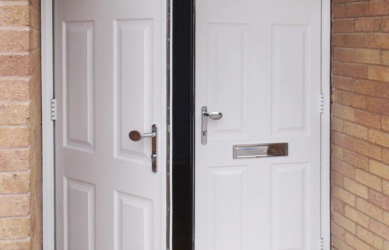 A partially open double entrance door in white