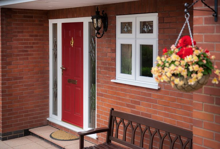Red UPVC door with golden knocker.