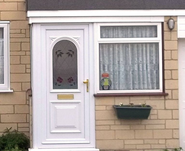 White UPVC entrance door with rose leading.