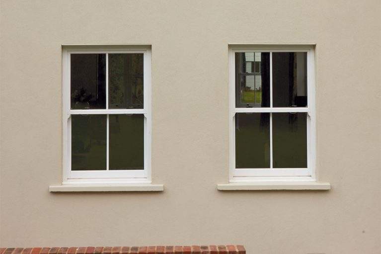 White UPVC vertical slider window with sash horns and window bars.