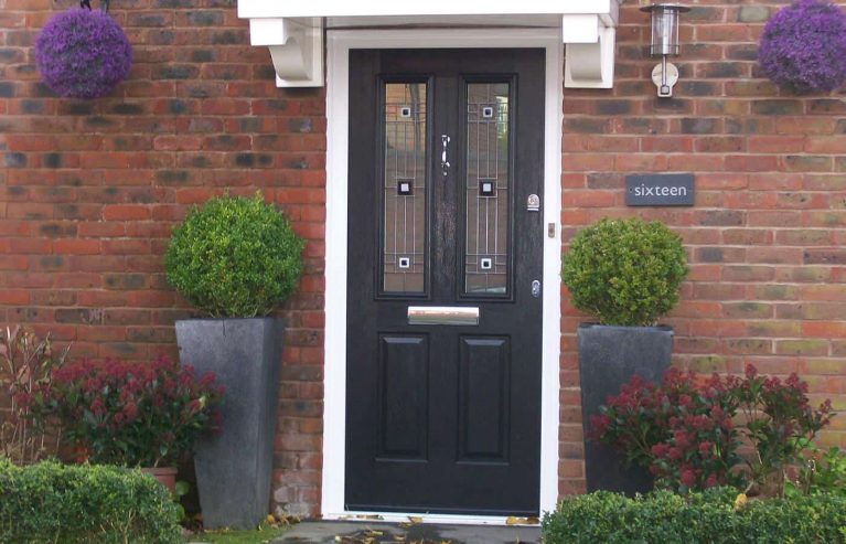A black composite front door with lead detail