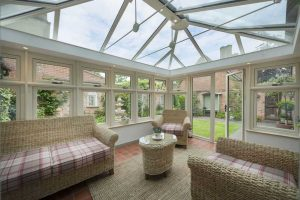 Am interior photo of a conservatory with a glass roof and double glazed windows and doors