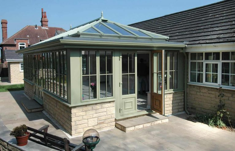 A traditional sage green uPVC orangery