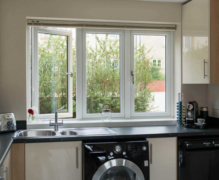 White UPVC flush sash windows with blinds in a kitchen.
